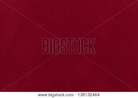 Dark red suede fabric closeup. Velvet texture background