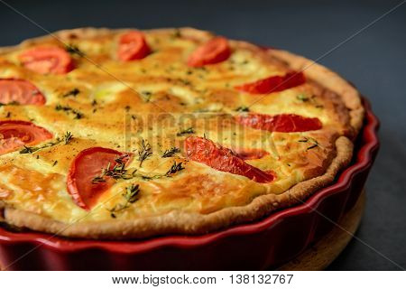Close-up cropped photo of classic quiche lorraine pie with tomatoes, over grey textural surface