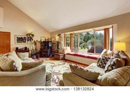 Living Room Interior With Vaulted Ceiling And Cozy Sitting Place With Red Pillows.