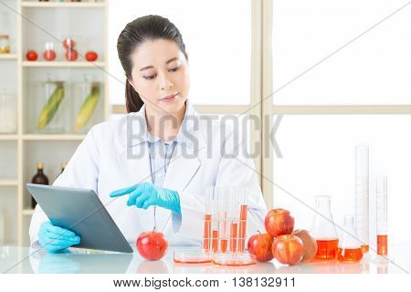 Asian Female Scientist Touch The Digital Tablet To Research