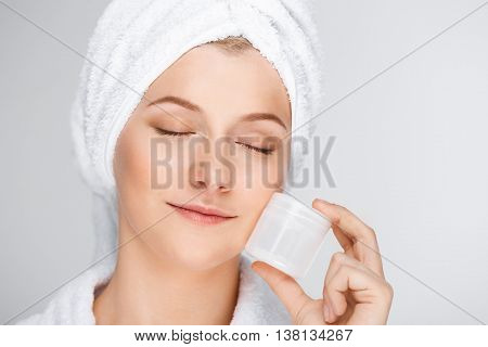 Portrait of blonde young pretty girl in bathrobe with towel on head, holding cream in hand, smiling, eyes closed, over white background.