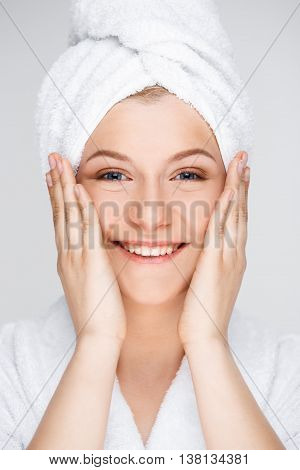 Portrait of blonde young pretty girl in bathrobe with towel on head, smiling, looking at camera, hands on cheeks, over white background.