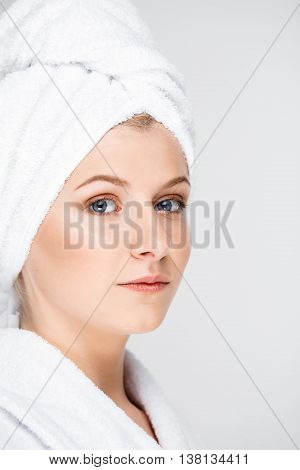 Portrait of blonde young pretty girl in bathrobe with towel on head, looking at camera, over white background.
