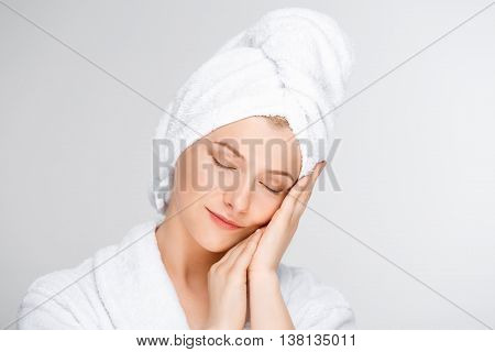 Portrait of blonde young pretty girl in bathrobe with towel on head, smiling, eyes closed, hands on cheek, over white background.