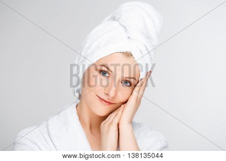 Portrait of blonde young pretty girl in bathrobe with towel on head, smiling, looking at camera, hands on cheek, over white background.