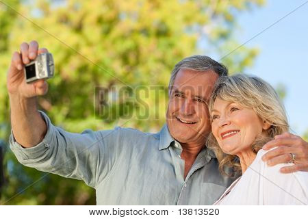 Smiling Couple Taking A Photo Of Themselves In The Park