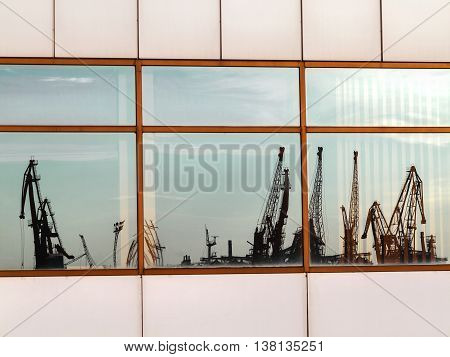 Silhouette Of Marine Cranes In The Backlight Is Reflected In The Windows Of Seaport