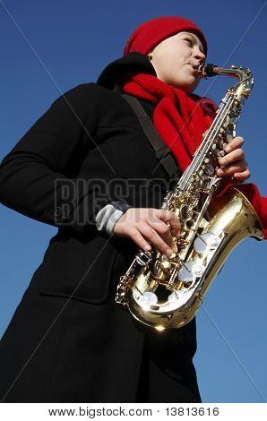 Beautiful girl plays on a saxophone