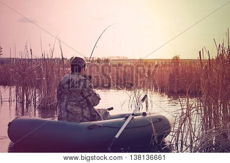 fisherman in a boat on the lake vintage toning