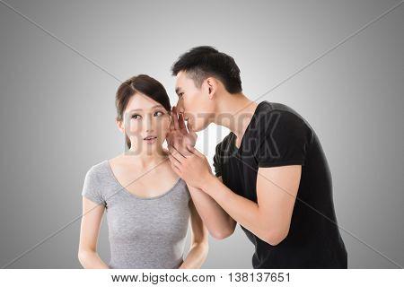 young Asian couple whisper, closeup portrait.