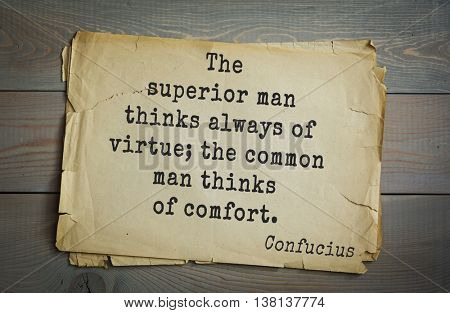 Ancient chinese philosopher Confucius quote on old paper background. The superior man thinks always of virtue; the common man thinks of comfort.