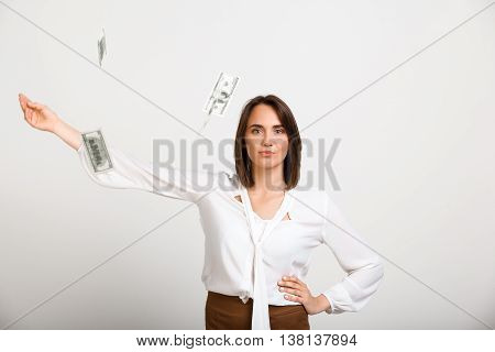 Portrait of young successful business woman looking at camera, throw up money, over white background.