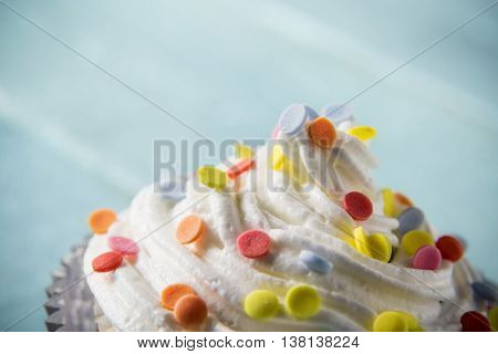 One nicely decorated muffin with cream and colorful sprinkles placed on light blue wooden boards background