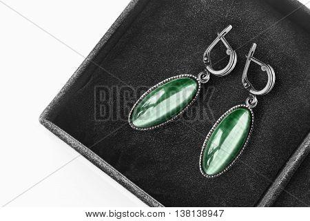 Green emerald earrings in black jewel box as a background