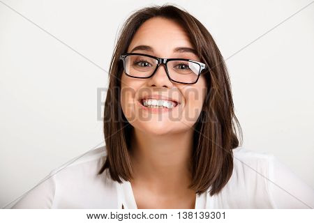 Portrait of young beautiful girl in glasses playing ape, smiling over white background.