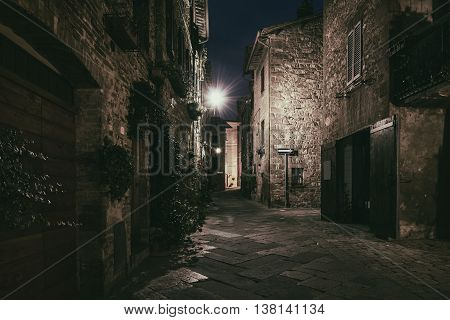 Night view of beautiful Italian medieval Pienza city with lanterns. Travel outdoor Tuscany background. Dark grungy gothic halloween concept.