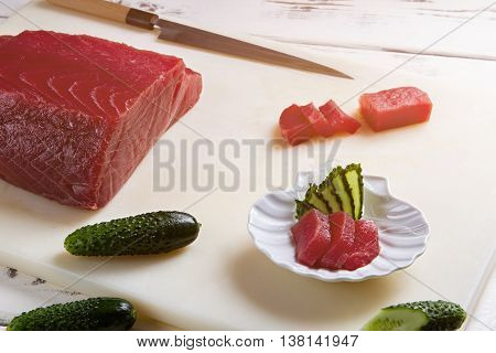 Pieces of fish and cucumber. Sliced cucumber and raw fish. Tuna for makizushi. Recipe of traditional japanese dish.