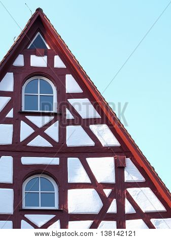 Gable and façade details of an old timber frame medieval house with white render and red beams in Nuermberg 2016
