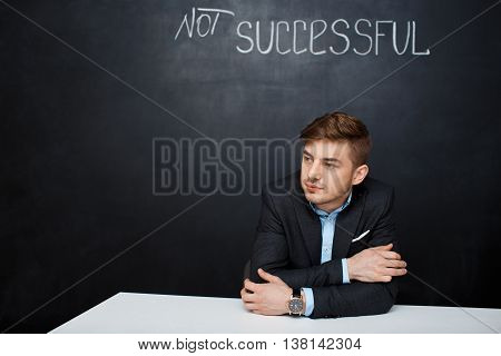 Picture of a  suited, sad man over black board with a text not successful. Looking left.