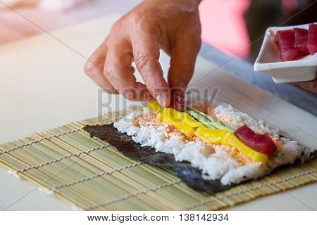 Hand puts piece of fish. Raw fish and white rice. Tuna for hosomaki rolls. Preparation of sushi in restaurant.