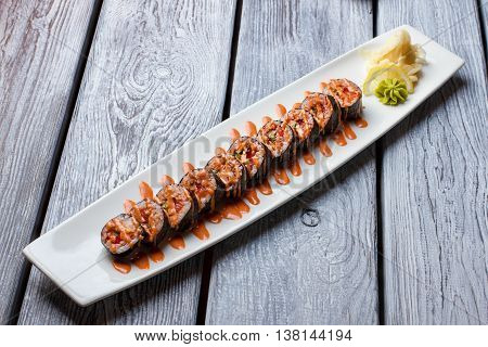 Long white plate with sushi. Sushi rolls and wasabi. Dinner served at sushi restaurant. Greetings from Japan.