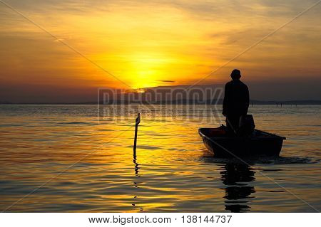 Silhouette of fisherman on boat in the sunrise at Labuan island,Malaysia.