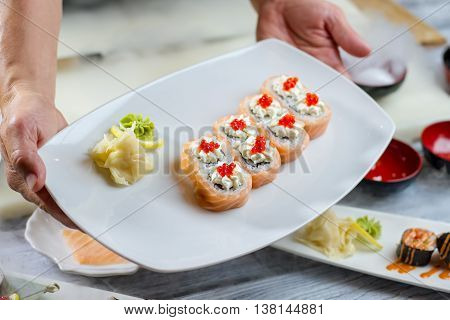 Hands hold plate with sushi. Sushi with lemon and wasabi. Salmon caviar on uramaki rolls. Japanese meal with spices.