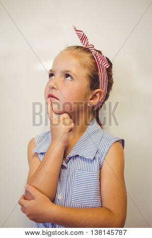 Thoughtful cute girl with hand on chin in classroom at school