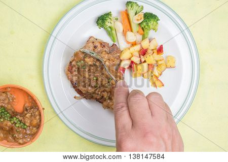 Chef puted gravy sauce to pork chop steak / cooking porkchop steak concept