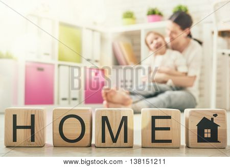 Happy loving family playing with blocks and having fun. Blocks have letters. Mother and her daughter lay out cubes and word home.