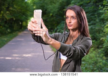 Beautiful woman taking pictures of herself outdoor