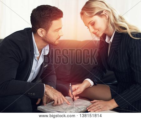 Young manager flirting with businesswoman in sunset review contract indoors