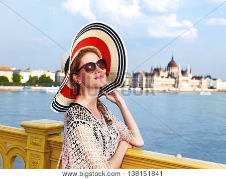 Young woman on Margaret bridge Budapest blue Danube with Parliament Hungary