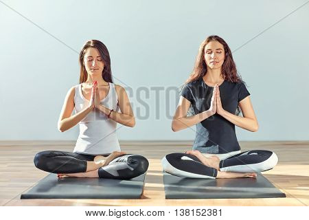 Two Young Women Meditating In Lotus Pose With Hands In Namaste