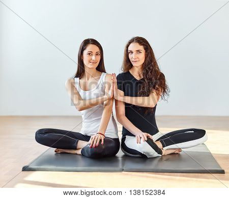 Two young women doing namaste in lotus pose at a fitness studio. Hand To Hand