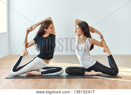 Two Young Women Doing Yoga Asana Eka Pada Rajakapotasana