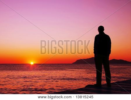 Man silhouette on the sunset on sea pier
