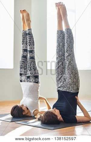 Two Young Women Doing Yoga Asana Supported Shoulderstand