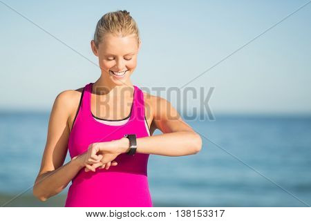 Happy young woman in sportswear checking time on beach
