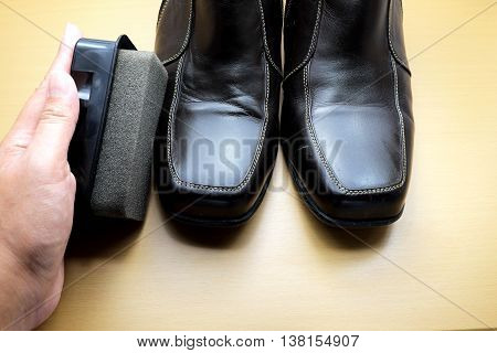 Shoe polishing brush with hand and brown leather shoe on wooden floor.