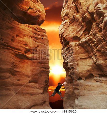 Menina escalada nas paredes do cânion no pôr do sol