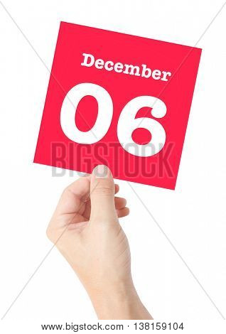 December 6 written on a card held by a hand