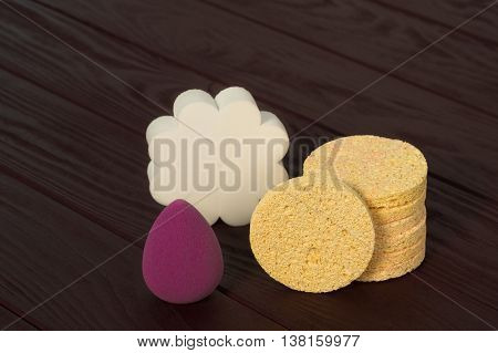 Still life white, yellow and purple make up sponges on dark wood background closeup
