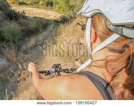 wide angle view of a woman about ready to ride her mountain bike down a steep hill in the back country