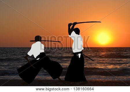 Two men are practicing Aikido at sunrise
