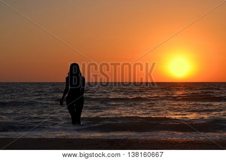 Silhouette of a girl in the water at sunrise