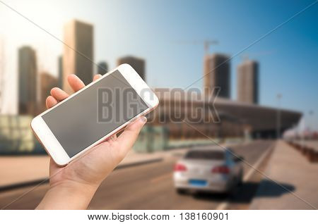 Hand holding smartphone with car driving on city road background
