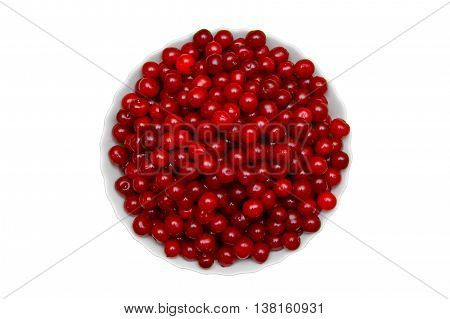 Set of beautiful red cherry in a glass dish on green background.