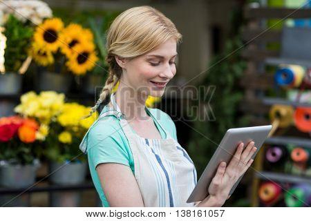 Smiling female florist using digital tablet in florist shop