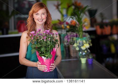 Portrait of female florist holding flower bouquet at flower shop